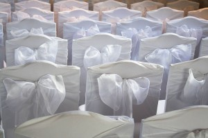 detail of chair back decorated for a wedding. white bows on white covers