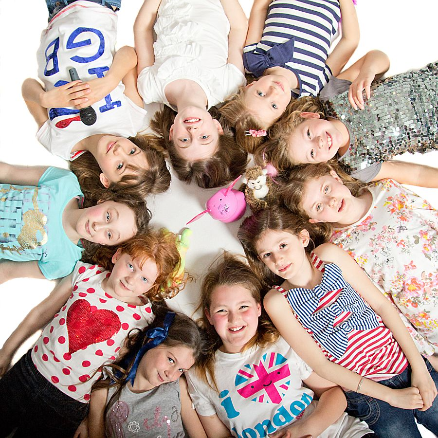 Group of young girls laying on their backs with heads meeting looking up at the camera