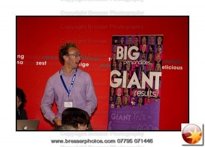 Luke Quilter, Big Giant adressing an audience with his company pull up banner beside him
