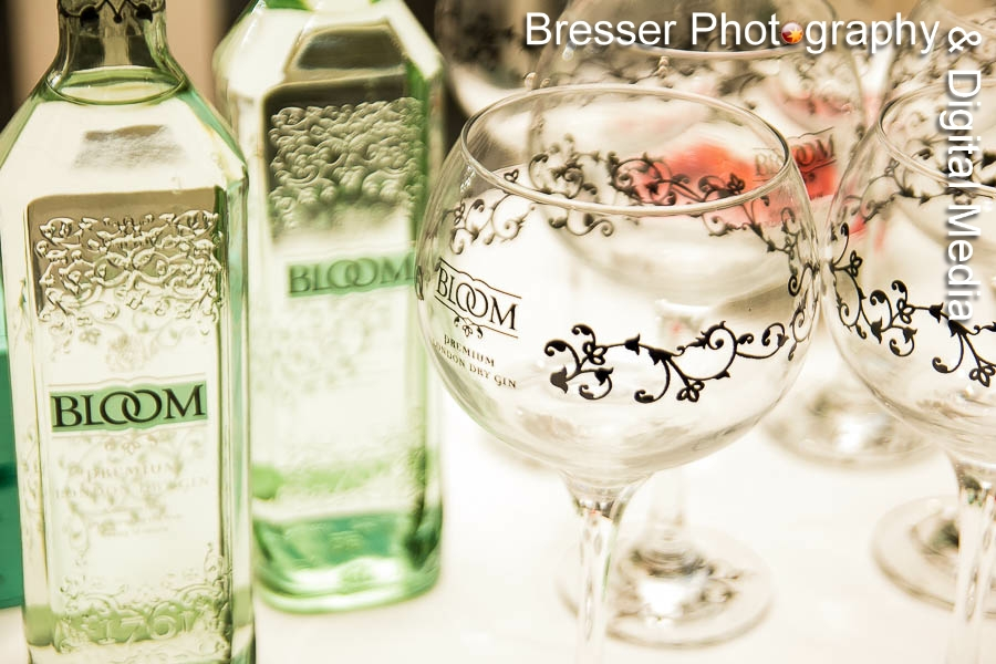 Bottles of Bloom branded gin with large goblet glass in foreground