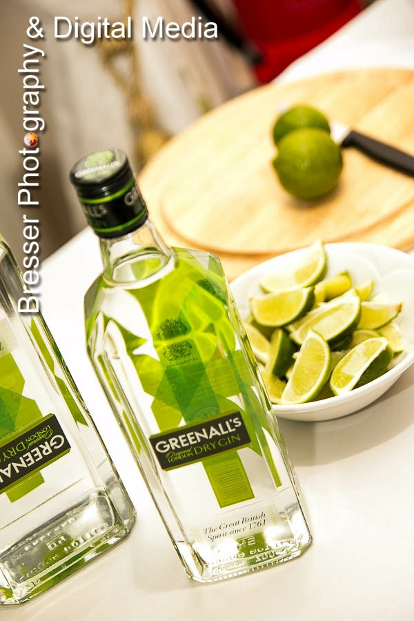 bottles of Greenhals branded gin with wedges of lime and whole limes in the background on a cutting board