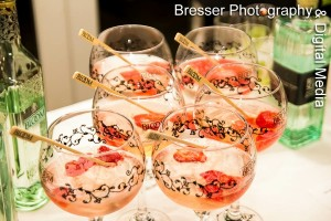 Six large goblet glasses containing Bloom gin, mixed with tonic water and crushed strawberries beside gin bottles
