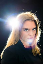 head and shoulders portrait of Zoe Clews, Hypnotist, with black background and heavy lens flare from light source over her shoulder