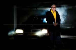 commercial portrait photograph of man and car in moody dark surroundings