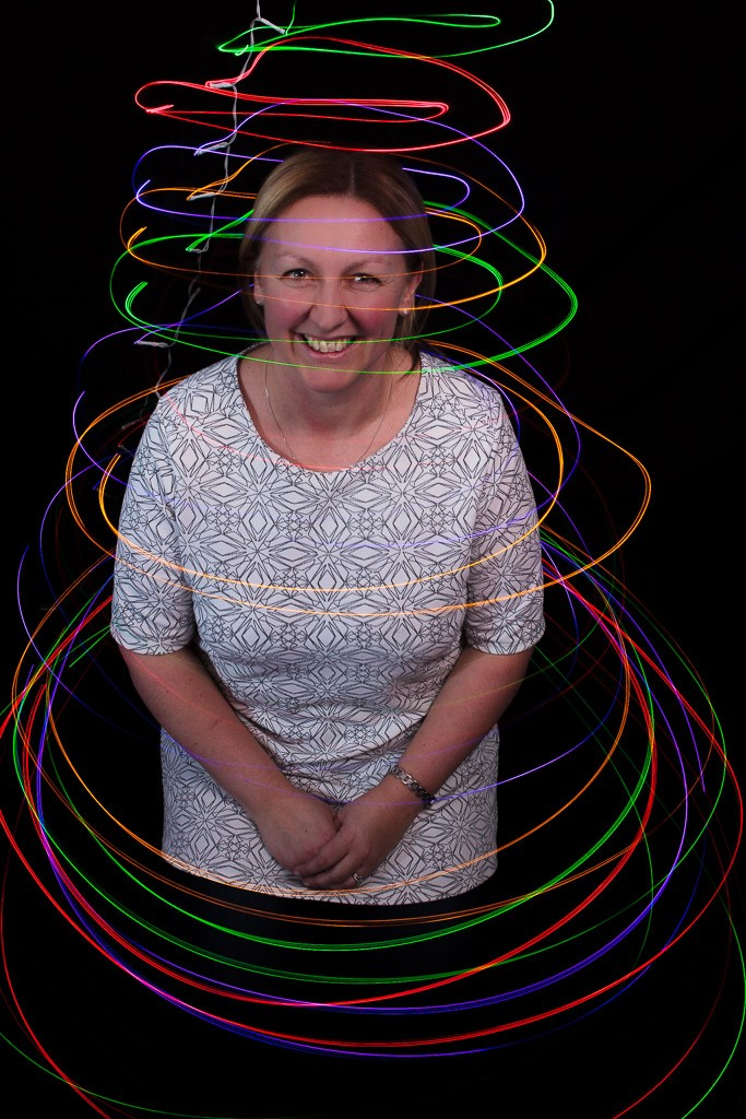 portrait of a woman against a dark background with light trails around her in multiple colours