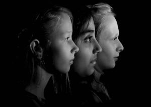 black and white head shot portrait of three children in profile