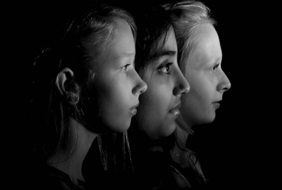 black and white head shot portrait of three children in profile