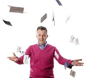 portrait of man with business cards 'flying' around him