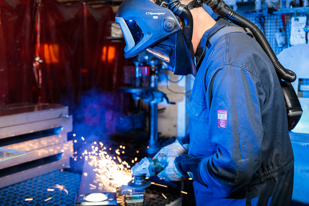 Man using grinder on metal producing sparks. He wears protective clothing